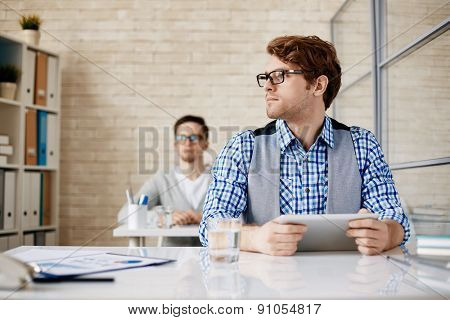 Young male employee with touchscreen gadget working in office