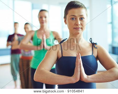 Pretty female doing yoga exercise with several people behind