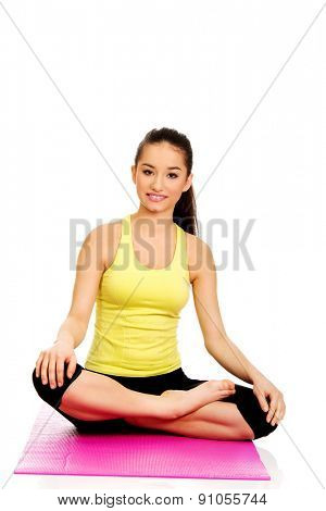 Fitness woman sitting cross legged on exercise mat.