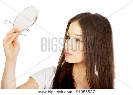 Young teenage woman holding a mirror.