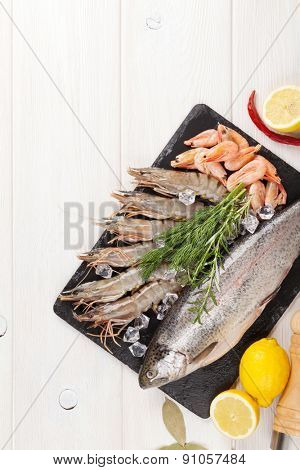 Fresh raw sea food with spices on wooden table background. Top view with copy space