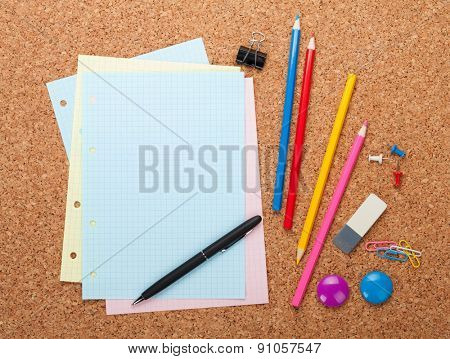 Blank notepad page on cork wood notice board with office supplies