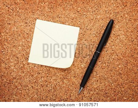 Blank postit note on cork notice board with pen