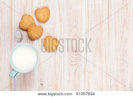 Cup of milk and heart shaped cookies on white wooden table with copy space
