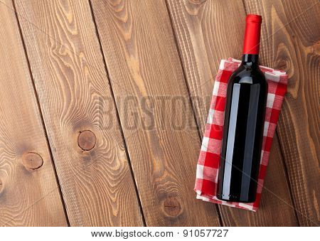 Red wine bottle over towel on wooden table background. Top view with copy space