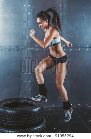 Sporty active fit woman box jumping. Female athlete is performing tire jumps fitness, sport, trainin