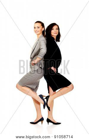 Two happy businesswomen leaning on each other.