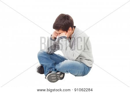 Sad preteen boy sitting on the floor isolated on a white background