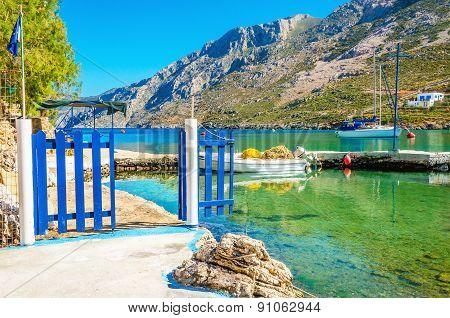Small port with boat and blue gate, Greece