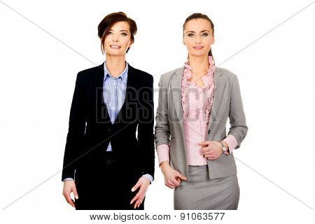Beautiful two businesswomen wearing office outfits.
