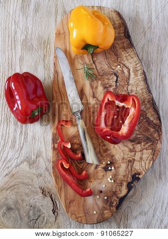 Red And Yellow Peppers On Olive Wood  Board