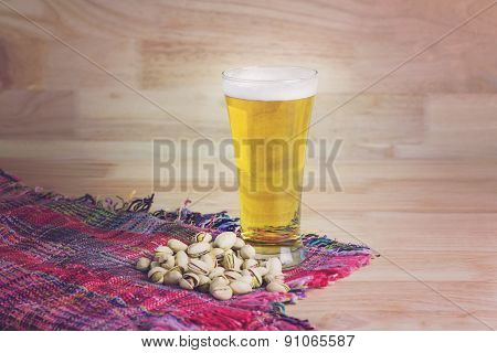 Glass Beer And Pistachios On Wood Background