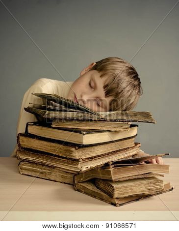 The Teenage boy sleeping on books, smiling