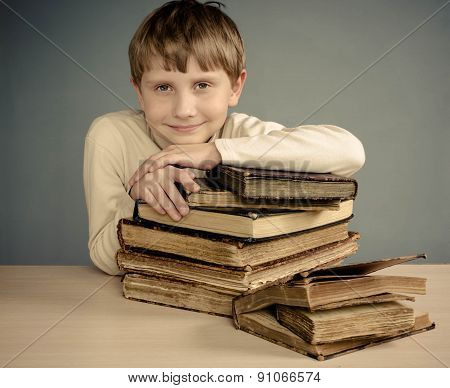 Teenage boy sleeping on books, smiling