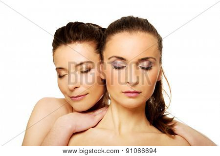 Two attractive sisters with make up and eyes closed.