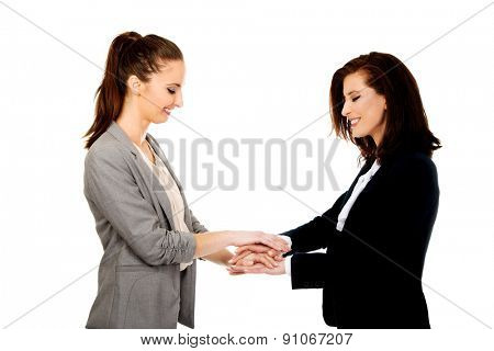 Two happy businesswomen holding their hands together.