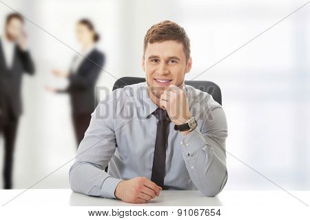 Happy businessman sitting by a desk in the office.