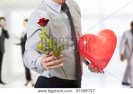 Young handsome man with a red rose and heart balloon.