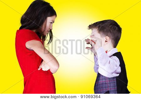 Sister and brother siting in front of each other with mad,mean,rivalry emotions over yellow