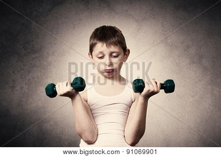 Tired,Bored,upset little boy with dumbbell.Facial expression,Sport.