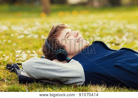 Young student, man relaxing smiling while lying on grass and listening to music.Player.Music,Relax