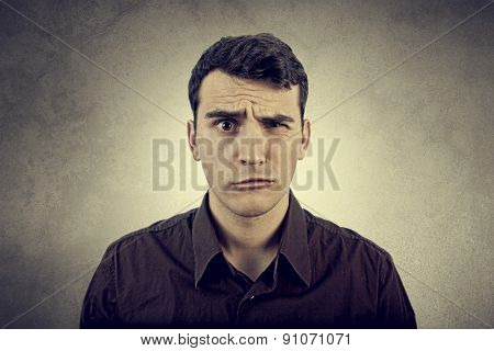 Disgusting expression.Portrait of disgusted man over grey background.