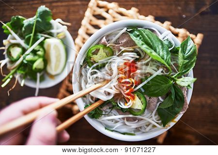 vietnamese pho with spicy sriracha sauce shot top down
