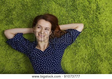 Happy woman lying down dressed in a black dress with white dots on green artificial grass.
