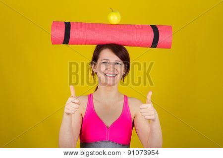 Sporty fit healthy smiling beautiful woman, red head girl holding  an yoga mat on her head with thum
