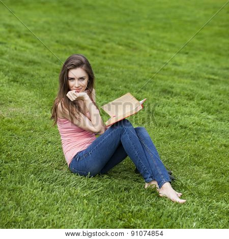 Young beautiful woman reading a book outdoor