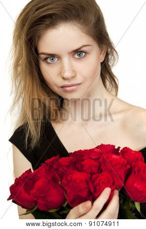 Portrait of a young beautiful blonde girl with a bouquet of red roses, isolated on white background