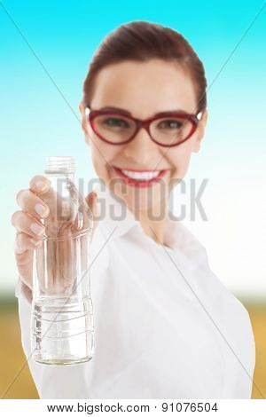 Beautiful thirsty businesswoman with bottle of water.