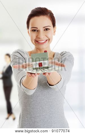 Happy woman holding dollar banknotes and house.