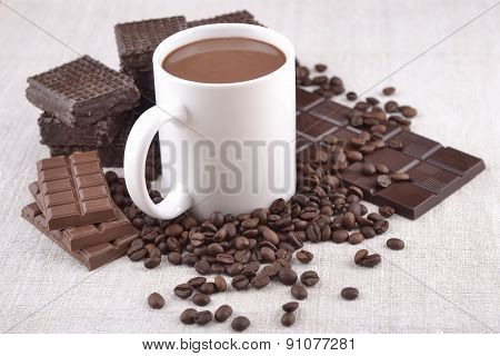 White Cup Of Hot Chocolate On Coffee Beans And Chocolate Background