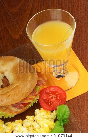 Bacon And Cheese Bagel With Scrambled Eggs And Juice