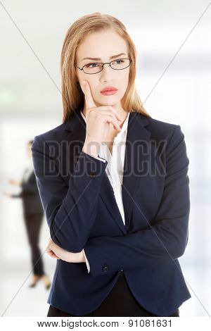 Beautiful young pensive business woman in glasses.