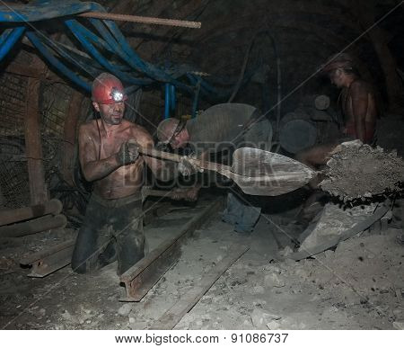 Donetsk, Ukraine - August, 16, 2013: Miners Perform Heavy Manual Labor In Low Light Conditions And D