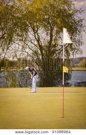 Male senior golf player putting on green with flag in foreground.
