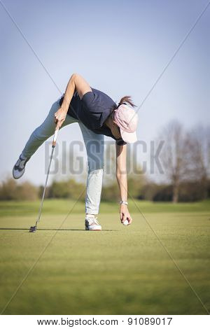 Female golf player picking up golf ball from hole on green.