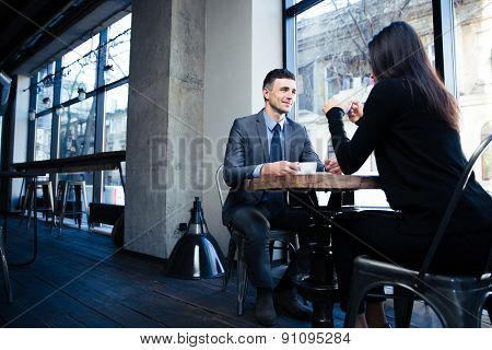 Happy businessman and businesswoman sitting at the table with coffee in restaurant