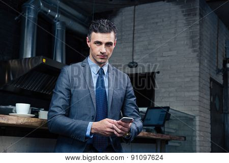 Handsome businessman using smartphone in cafe and looking at camera