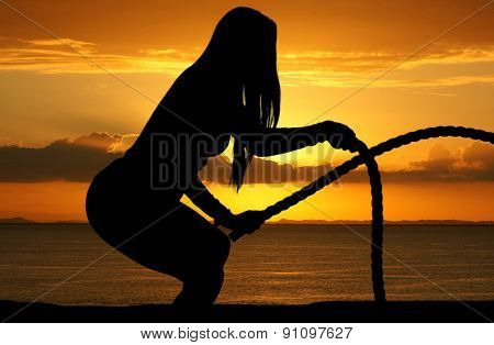 Woman who is working out on the beach with a sunset