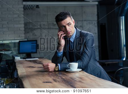 Pensive handsome businessman talking on the phone in cafe and looking away
