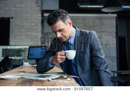Confident businessman reading magazine and drinking coffee in cafe