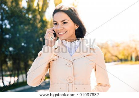 Cheerful woman talking on the phone outdoors and looking away