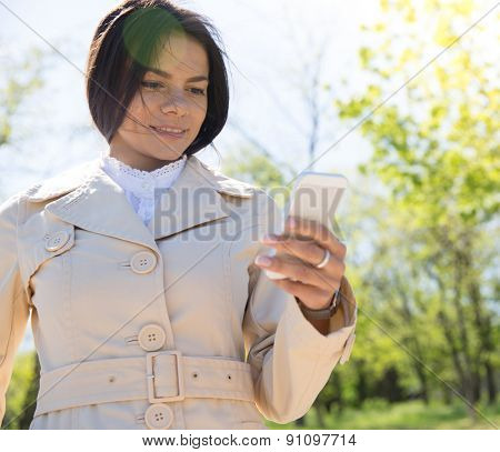 Happy cute woman using smartphone outdoors