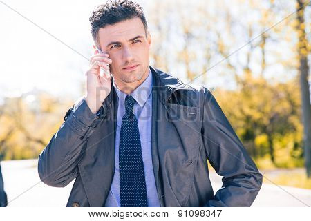 Confident businessman in suit talking on the phone outdoors and looking away