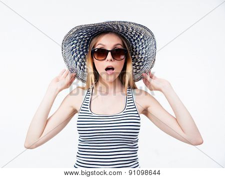 Amazed young woman in hat and sunglasses looking at camera over gray background