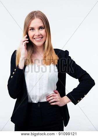 Smiling businesswoman talking on the phone isolated on a white background. Looking at camera
