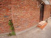 pic of distort  - The facade of the old brick with a door and a porch and along the wall grows wild grapes shot with a wide angle and distortion - JPG
